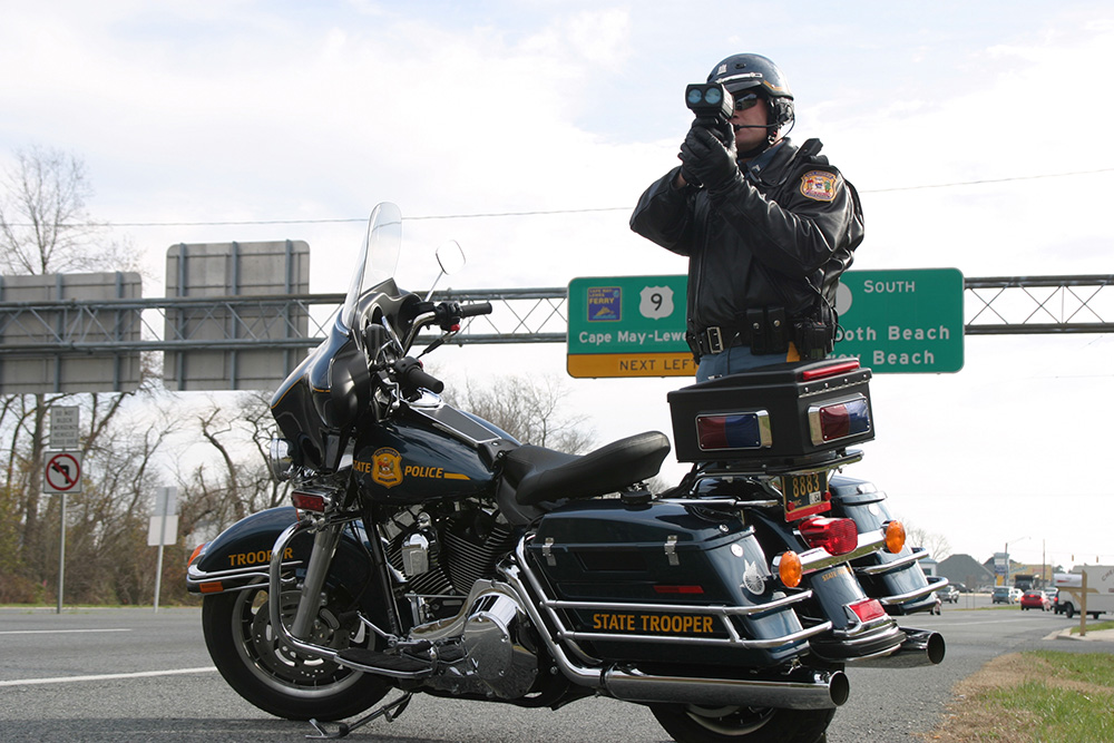 A trooper standing near his motorcycle on duty shooting radar