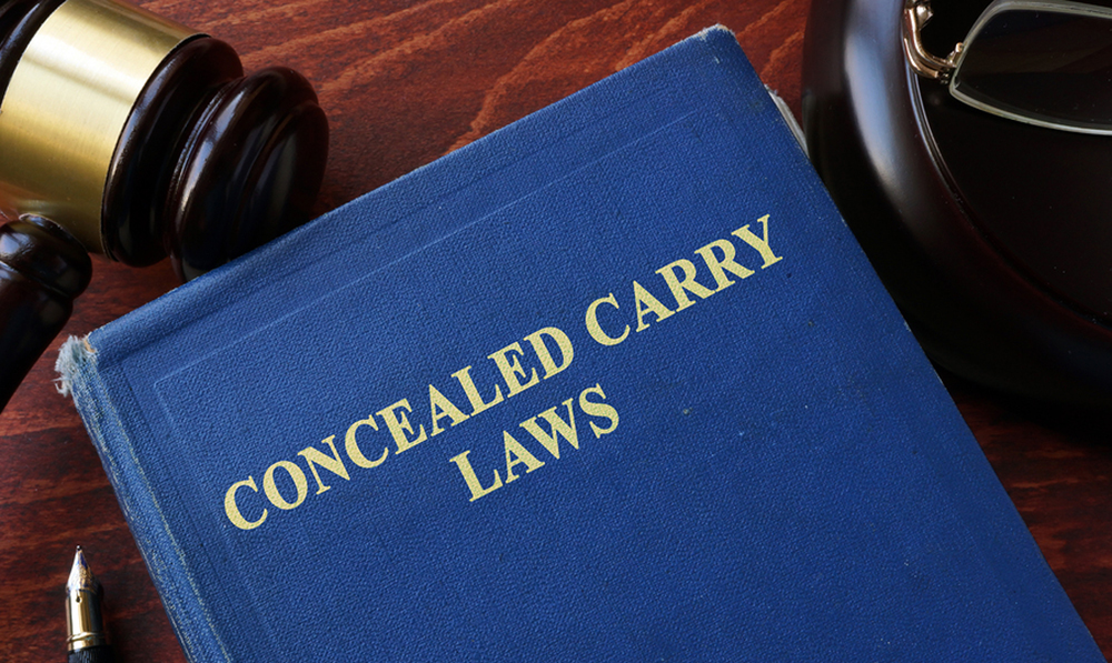 A book with the text Concealed Carry Laws and a gavel in the background