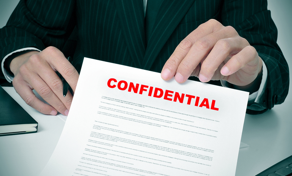 a man wearing a suit showing a document with the text confidential