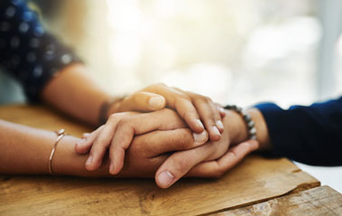 Two people holding hands representing Victim Services