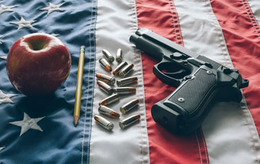 Apple, pencil, bullets and fun on top of American Flag